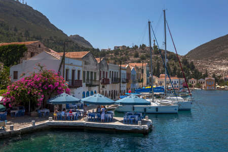 Tourist sit at a restaurant on the harbour on Kastellorizo Island (Meis) in Greece. The island is located only 2 kilometres from the Turkish coastline.