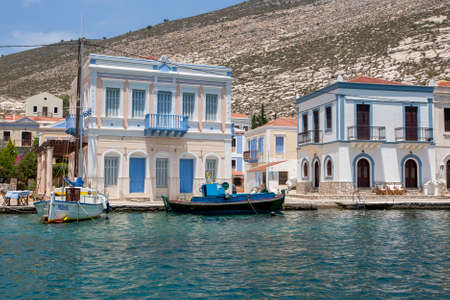 KASTELLORIZO ISLAND, GREECE - JUNE 21, 2010 : Boats docked adjacent to houses located on the harbour on Kastellorizo Island (Meis) in Greece. The island is located only 2 kilometres from the Turkish coastline.