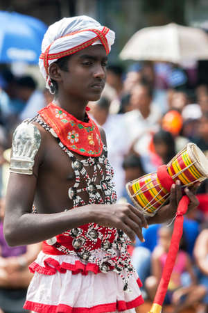 An Udekki Player  performs along a street in Kandy during the Day Perahera (great procession), the final event of the Buddhist Esala Perahera. Editorial