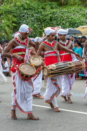 A Thammattam Player and two Gatabera Players perform along a street in Kandy, Sri Lanka during the Day Perahera, the final event of the Buddhist Esala Perahera.