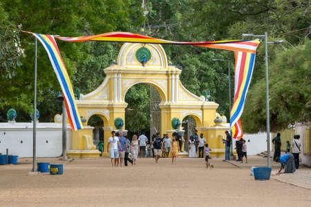 Visitors walk past the main entrance arches to the Kataragama temple in central Sri Lanka.