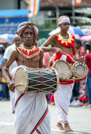 A Davul Player beats his drum whilst performing along a street in Kandy, Sri Lanka during the Day Perahera, the final event of the Buddhist Esala Perahera.