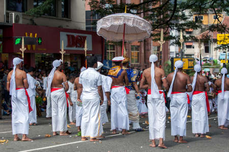 Spear Bearers surround a Buddhist Temple Custodian as he parades along a street in Kandy during the Day Perahera, the final event of the Buddhist Esala Perahera. Editorial