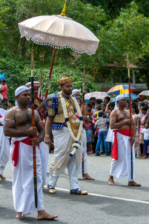 A Buddhist Temple Custodian sheltered by an umbrella walks along a street in Kandy, Sri Lanka during the Day Perahera, the final event of the Esala Perahera. He is accompanied by  Spear Bearers. Editorial