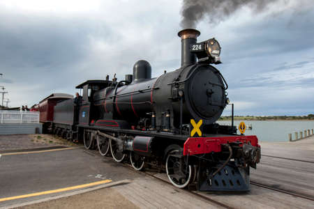 The Cockle Train driven by RX 224, a 1915 built steam locomotive, departs Goolwa station in South Australia, Australia. The train is run by the SteamRanger Heritage Railway.