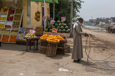 A man cutting a hose stands in front of a greengrocer store on the outskirts oft Cairo in Egypt.