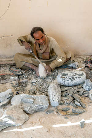 A man shapes a piece of stone using a metal file at an alabaster factory at Luxor in Egypt.