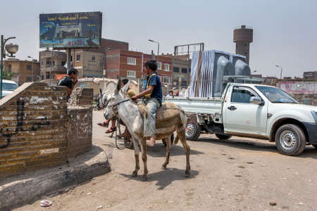 Boys riding donkeys stop on a bridge crossing a canal on the outskirts oft Cairo in Egypt.