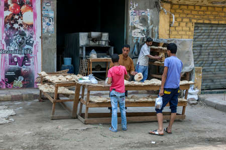 A man selling flat bread to a customer from a bakery on the outskirts of Cairo in Egypt.