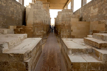 Tourists admire the stone carved columns of the Hypostyle Hall at the entrance to the Step Pyramid (Pyramid of Djoser) at Saqqara in northern Egypt.