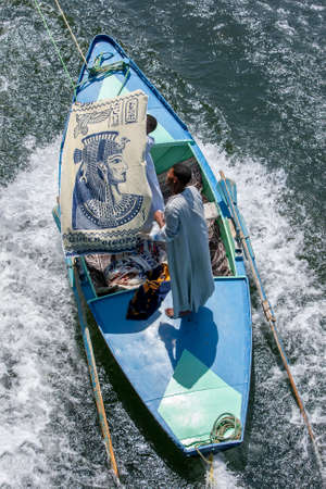 Textile salesman aboard a rowing boat attempt to sell a beautifully inscribed cloth to tourists on a floating hotel ship travelling along the River Nile from Luxor to Esna in Egypt. Editorial