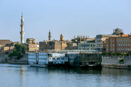 Floating hotel ships docked on the bank of the River Nile at Esna in central Egypt in the late afternoon.