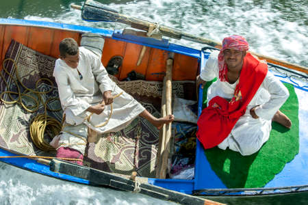 Textile salesman aboard a rowing boat being towed by a floating hotel ship travelling along the River Nile from Luxor to Esna in Egypt.