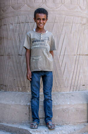 A smiling Egyptian boy stands in front of a giant stone column at the Temple of Horus at Edfu in central Egypt.