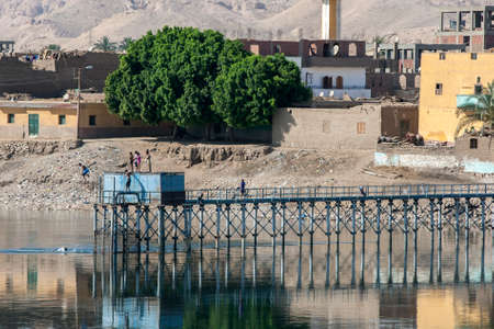 A man jumps from a water pumping station into the River Nile north of Esna in the afternoon.