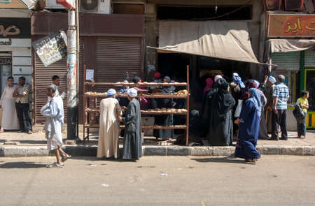 People crowd together at the entrance to a bakery on a street in Edfu in central Egypt. Editorial