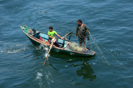 Fishermen in a rowing boat pull in their net on a section of the River Nile south of Luxor in central Egypt.