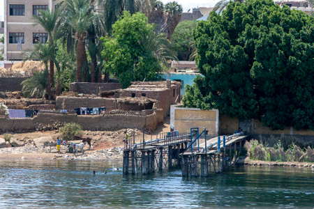 A scene from the bank of the River Nile showing a water pumping jetty and a mud brick house at Luxor in Egypt. Editorial