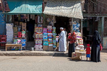 Women with children stand at at the entrance to a store selling nappies on a street in Edfu in central Egypt. Editorial