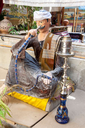 A seated manikin showing a man smoking from an Egyptian Hookah at the entrance to a restaurant at Luxor in central Egypt. Editorial