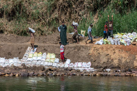 Workers sandbag a damaged section of the bank of the River Nile south of Edfu in central Egypt.