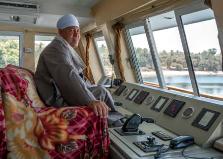 The captain of a floating hotel ship sits at the controls of his vessel as it travels down the River Nile from Edfu to Aswan in Egypt.