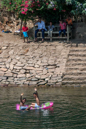 Egyptian boys play on an inflatable boat in the River Nile at Edfu in Egypt on a hot day.