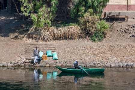 A man waits on the bank of the River Nile with food supplies to be picked up by a rowing boat south of Edfu in central Egypt.