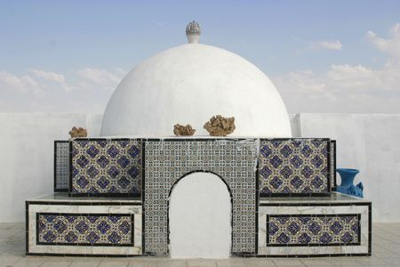 Decorative oriental, arab style cupola on top of the building in Tunisia with desert roses and vases on it Stock Photo