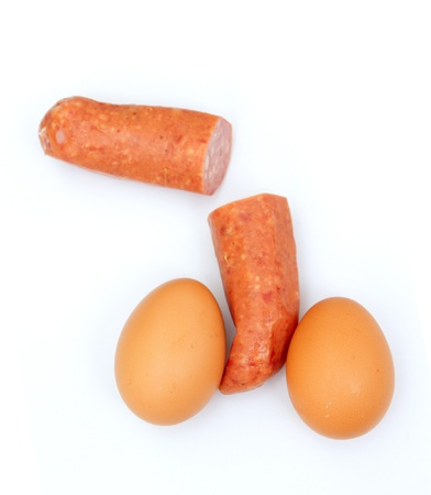 Two eggs and intersected sausage like testicles and penis Stock Photo