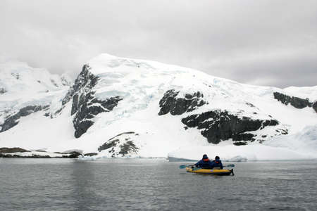 Two people in yellow kayak in Antarctica. Shore under snow and cloudy sky. Stock Photo