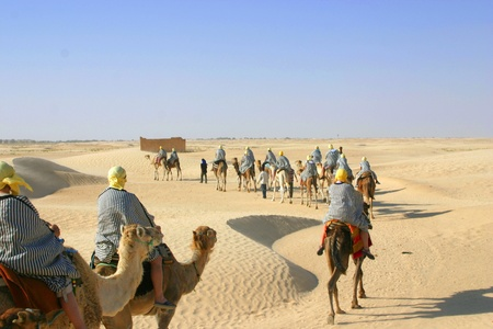 Group of tourists dressed like bedouins riding camels in line thorough Sahara desert in Tunisia Stock Photo