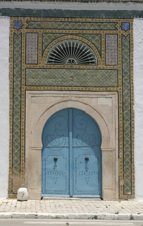 Blue door and detail of North African arab architecture - ornaments around the doors photo