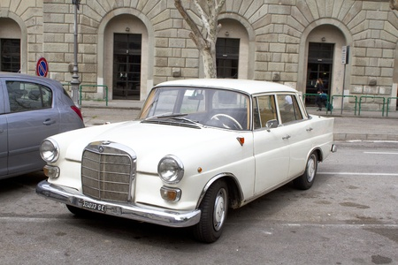 Trieste, Italy - April 7th 2011: Mercedes-Benz W110, white, model from sixtes parked on parking place in front of bus station.