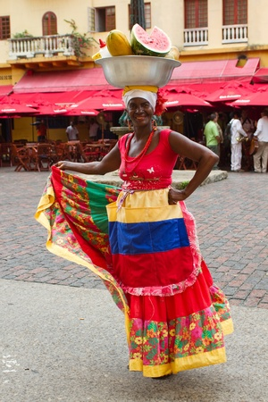 Cartagena, Colombia - December 13th 2010: Woman wearing trafitional Columbian dress and dish with fruit on her head.