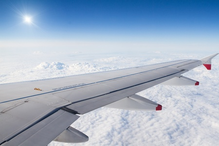 Airplane wing aboe the fluffy white clouds