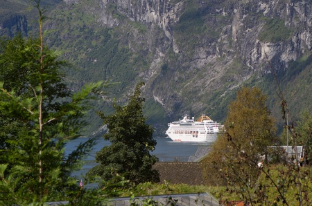 View at cruise ship through trees. Norway, Geiranger fjord