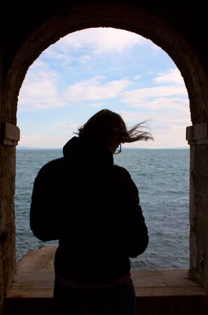 Silhouette of thinking woman on the arched window on old building. View of sea and sky through the window.  Stock Photo