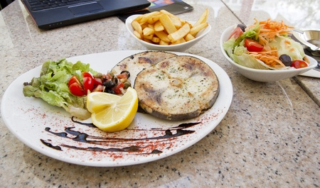 Swordfish steak served on the plate with lemon and vegetables and chips and salad on the side