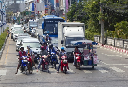 Pattaya, Thailand - March 5, 2012: Typical traffic scene in Pattaya. Motorcycles provide personal transportation. Auto rickshaws and buses provide public transportation. Trucks in a range of sizes haul goods.