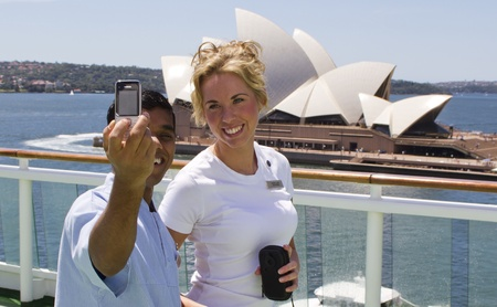 SYDNEY, AUSTRALIA - FEBRUARY 16: Young couple taking picture on cruise ship's deck with Sidney Opera house in the background on February 16, 2012 in Sydney, Australia