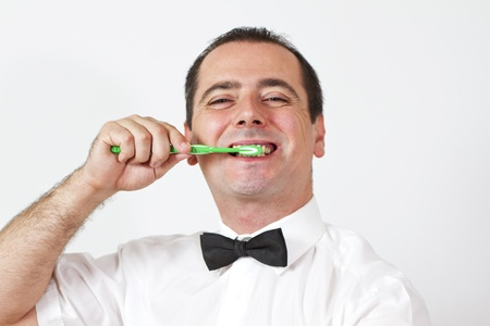 Guy with bow tie is brushing teeth and have awkward smile Stock Photo