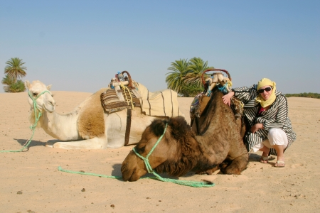 Young woman wearing desert clothes with camels in Sahara photo