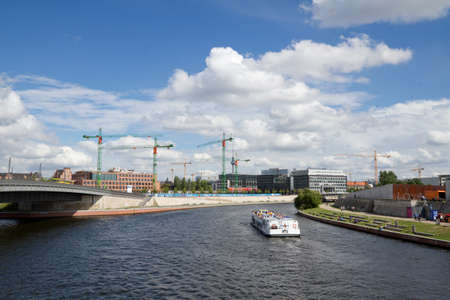 View at river Spree with boat sailing and construction in background, Berlin, Germany
