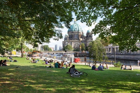 BERLIN, AUGUST 8: People enjoying in park by the river Spree on sunny summer day. Berliner dom is visible in background on August 8, 2012. Editorial