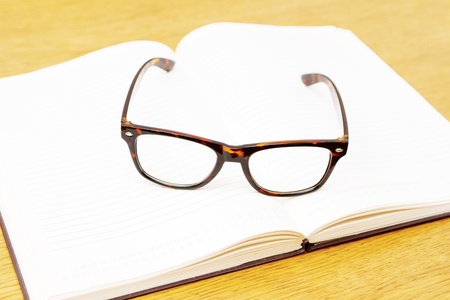 Modern glasses with plastic frames on open book Stock Photo