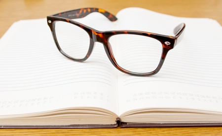 Modern glasses with plastic frames on open book photo