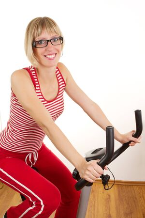 Young woman in red on exercise bike Stock Photo