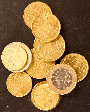 goldish: Euro coins on dirty dark background with goldish light effect