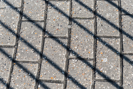 Diagonal shadows of railing on the pavement on a sunny February day in London, United Kingdom